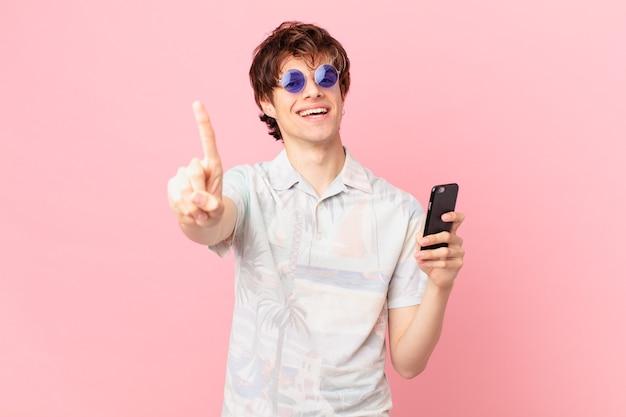 Jovem com um telefone celular sorrindo com orgulho e confiança alcançando o primeiro lugar