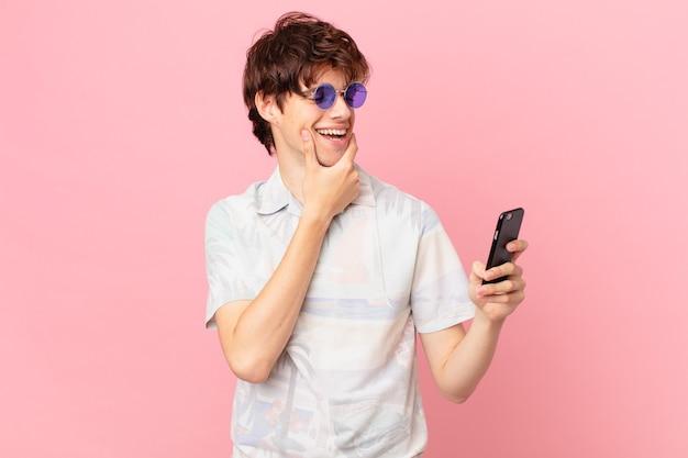 Jovem com um telefone celular sorrindo com uma expressão feliz e confiante com a mão no queixo