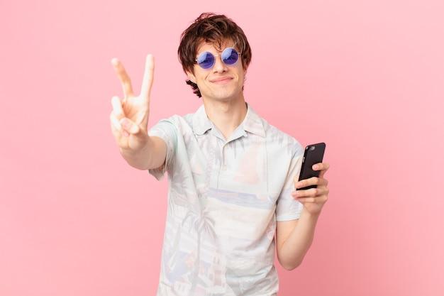 Jovem com um telefone celular sorrindo e parecendo amigável mostrando o número dois