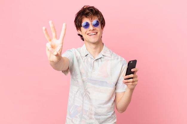 Jovem com um telefone celular sorrindo e parecendo amigável mostrando o número três