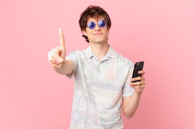 Jovem com um telefone celular sorrindo e parecendo amigável mostrando o número um
