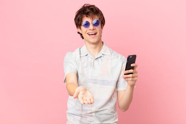 Jovem com um telefone celular sorrindo feliz com simpatia e oferecendo e mostrando um conceito