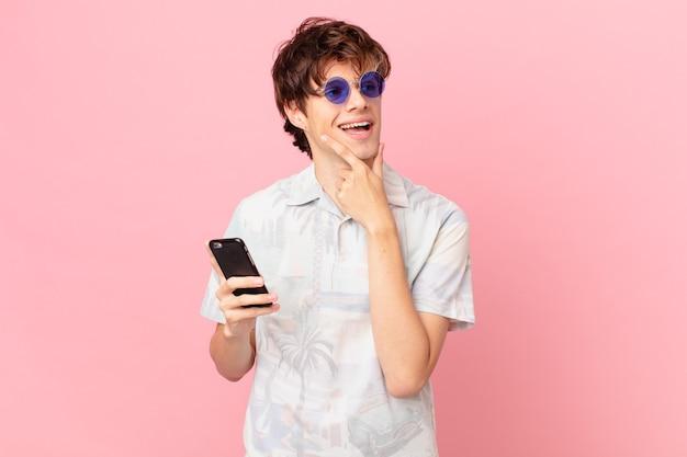 Jovem com um telefone celular sorrindo feliz e sonhando acordado ou duvidando