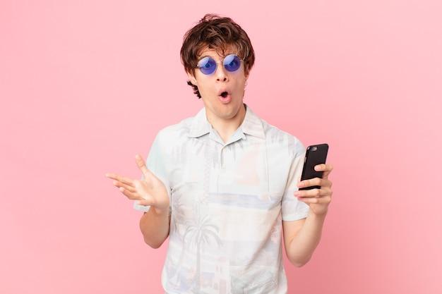 Jovem com um telefone celular surpreso chocado e surpreso com uma surpresa inacreditável
