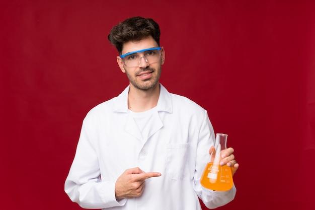 Jovem com um tubo de ensaio científico e apontando-o