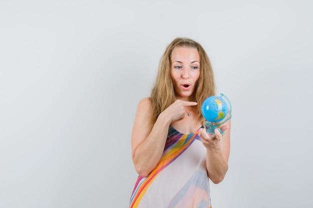 Jovem com um vestido de verão apontando para o globo terrestre e parecendo surpresa