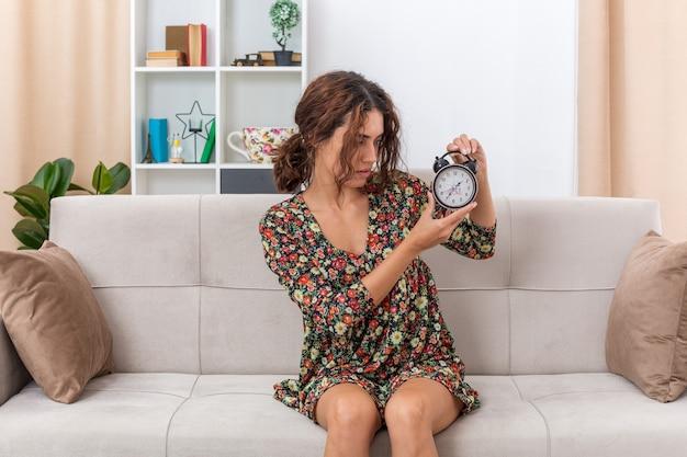 Jovem com um vestido floral segurando um despertador, olhando para ele com uma expressão confusa, sentada em um sofá na sala iluminada