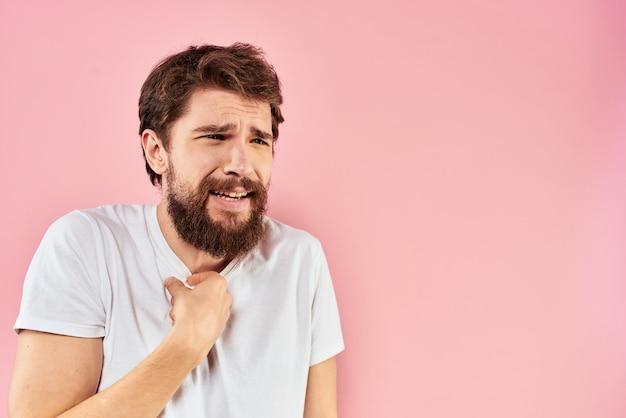 Jovem com uma barba em uma camiseta mostra emoções diferentes, diversão, tristeza