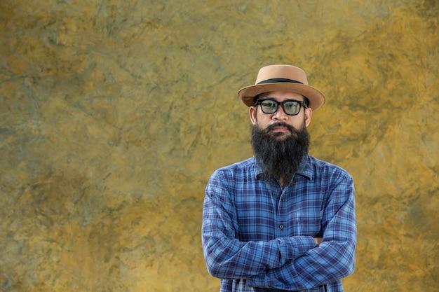 Jovem com uma barba longa, vestindo um chapéu e óculos