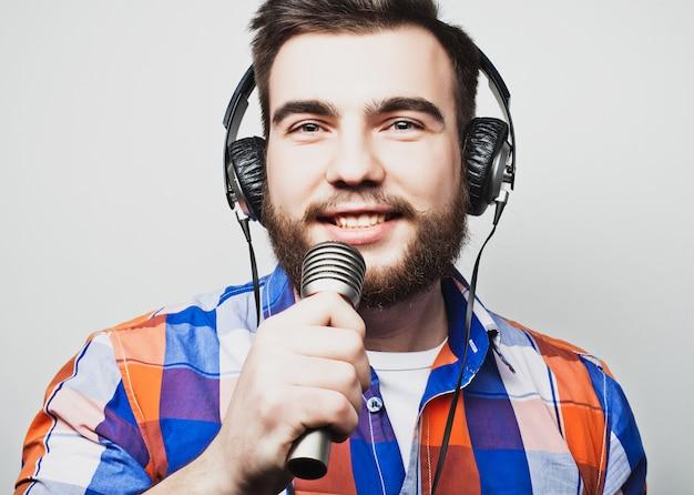 Jovem com uma barba, vestindo uma camisa, segurando um microfone