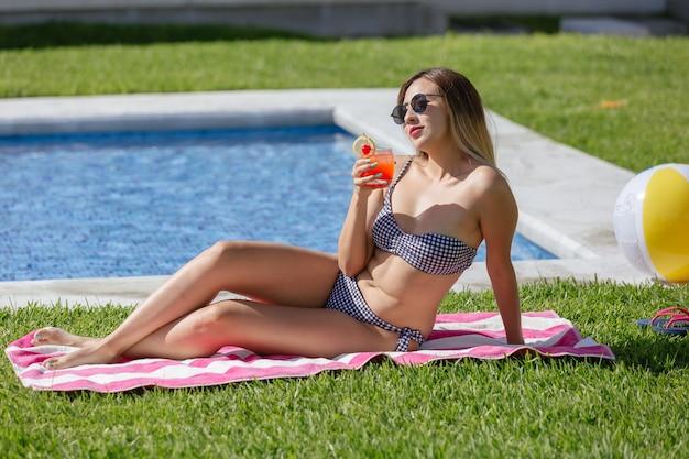 Jovem com uma bebida refrescante na mão, vestindo maiô e óculos escuros ao lado da piscina