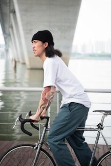 Jovem com uma bicicleta na cidade
