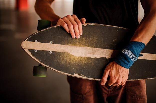 Jovem com uma braçadeira segurando um longboard