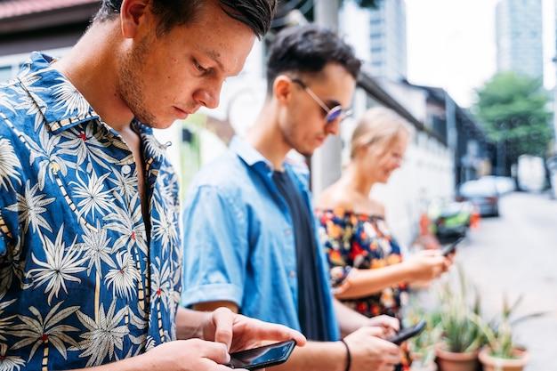 Jovem com uma camisa havaiana ao lado de dois jovens de diferentes etnias usando um celular no meio de uma rua com fachadas coloridas e arte de rua