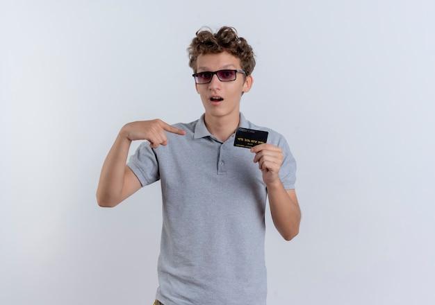 Jovem com uma camisa pólo cinza mostrando um cartão de crédito apontando com o dedo para ele sendo surpreendido em pé sobre uma parede branca