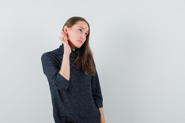 Jovem com uma camisa, segurando a mão atrás da orelha e parecendo curiosa