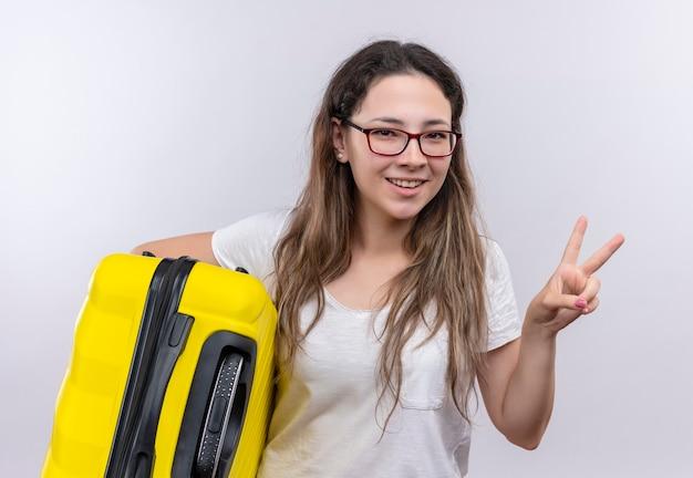 Jovem com uma camiseta branca segurando uma mala de viagem e sorrindo alegremente mostrando o sinal da vitória ou dois números