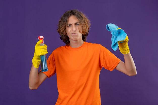 Jovem com uma camiseta laranja usando luvas de borracha, segurando um spray de limpeza e um tapete, olhando para a câmera com expressão cética no rosto em pé sobre um fundo roxo