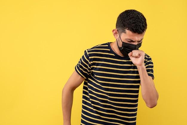 Jovem com uma camiseta listrada em preto e branco tossindo em um fundo amarelo de frente