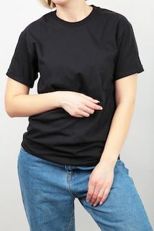 Jovem com uma camiseta preta em uma superfície cinza