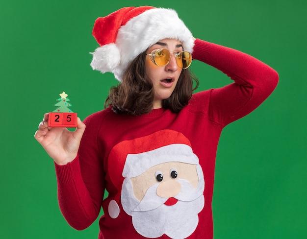 Jovem com uma camisola de natal com chapéu de papai noel e óculos segurando cubos de brinquedo com o número 25 olhando de lado, confusa com a mão na cabeça em pé sobre a parede verde