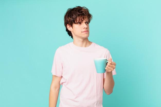 Jovem com uma caneca de café se sentindo triste, chateado ou com raiva e olhando para o lado
