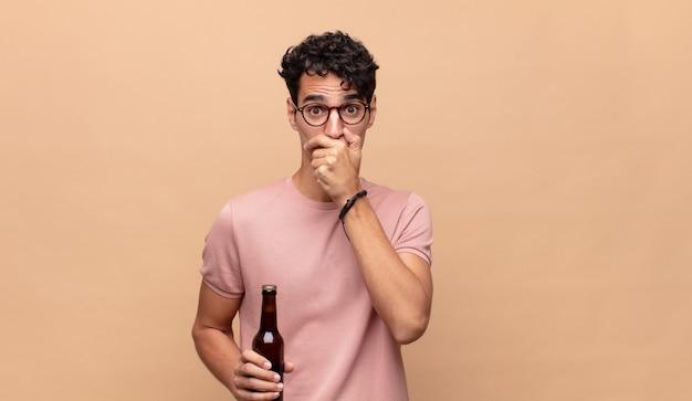 Jovem com uma cerveja cobrindo a boca com as mãos com uma expressão chocada e surpresa, mantendo um segredo ou dizendo oops