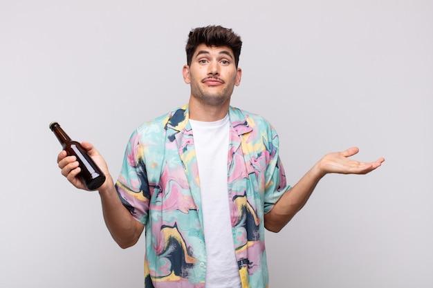 Jovem com uma cerveja se sentindo perplexo e confuso, duvidando, ponderando ou escolhendo opções diferentes com expressão engraçada