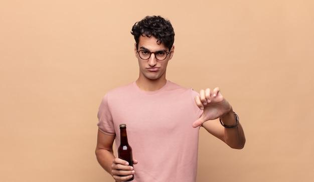 Jovem com uma cerveja, sentindo-se zangado, irritado, desapontado ou insatisfeito, mostrando o polegar para baixo com um olhar sério