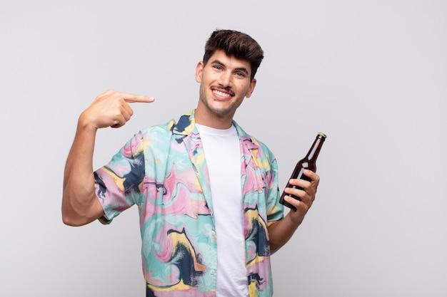 Jovem com uma cerveja sorrindo com confiança apontando para seu próprio sorriso largo, atitude positiva, relaxada e satisfeita