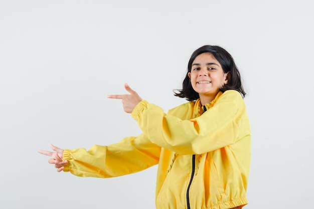 Jovem com uma jaqueta amarela apontando para a esquerda com o dedo indicador e parecendo feliz