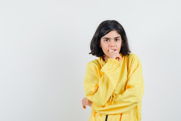 Jovem com uma jaqueta amarela mordendo os dedos e pensando em algo e parecendo pensativa