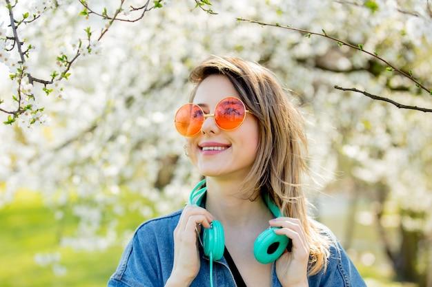Jovem com uma jaqueta jeans e fones de ouvido perto de uma árvore florida no parque. temporada de primavera