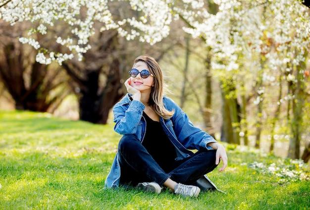 Jovem com uma jaqueta jeans e óculos escuros, sentada perto de uma árvore florida no parque. temporada de primavera