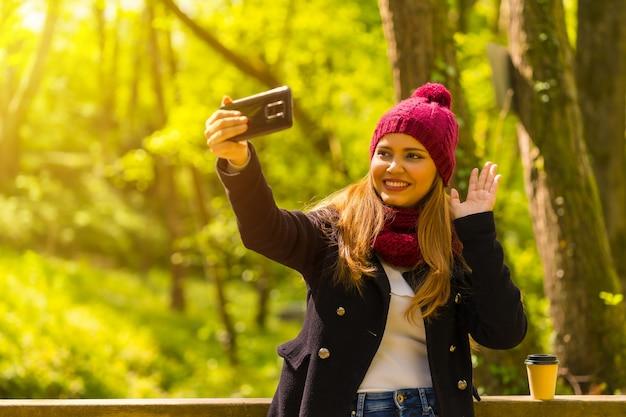 Jovem com uma jaqueta preta, cachecol e chapéu de lã vermelha, curtindo em um parque no outono, acenando em uma videochamada com o telefone