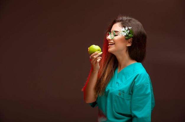 Jovem com uma maçã verde na mão e dando uma mordida.