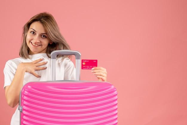 Jovem com uma mala rosa segurando um cartão de crédito de frente