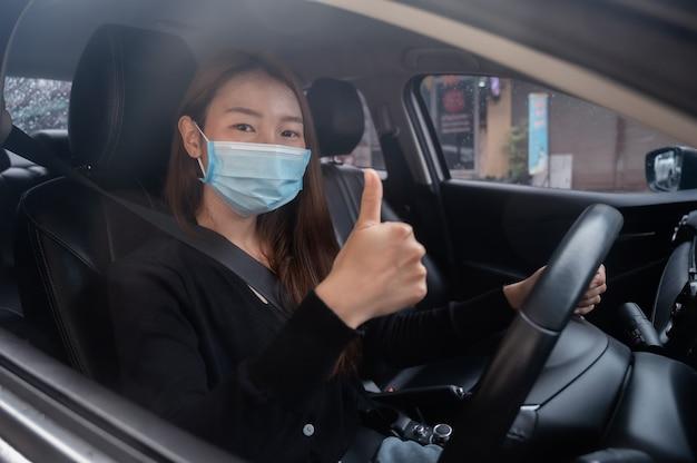 Jovem com uma máscara em um carro