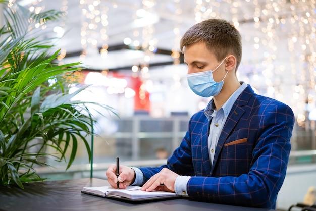 Jovem com uma máscara escreve em um caderno, um funcionário em um shopping center