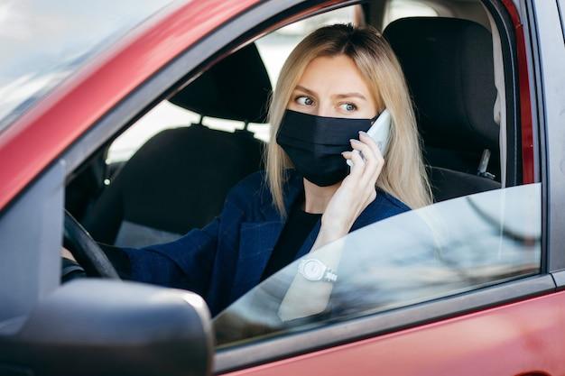 Jovem com uma máscara preta sentada em um carro e falando ao telefone