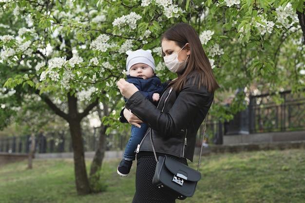 Jovem com uma máscara protetora, abraça seu filho pequeno