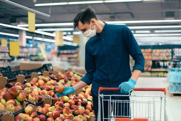 Jovem com uma máscara protetora em pé perto do balcão com maçãs. foto com uma cópia do espaço