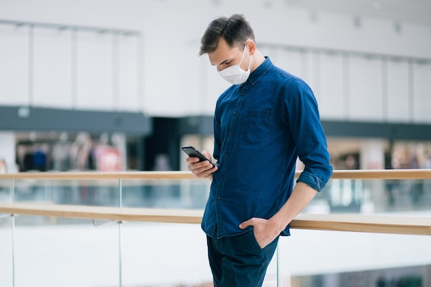 Jovem com uma máscara protetora lendo uma mensagem de texto em seu smartphone