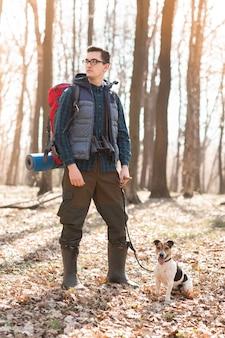 Jovem com uma mochila, binóculos e seu cachorro