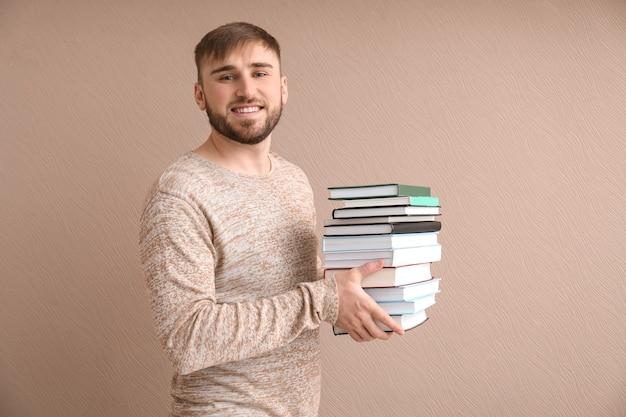 Jovem com uma pilha de livros na superfície colorida