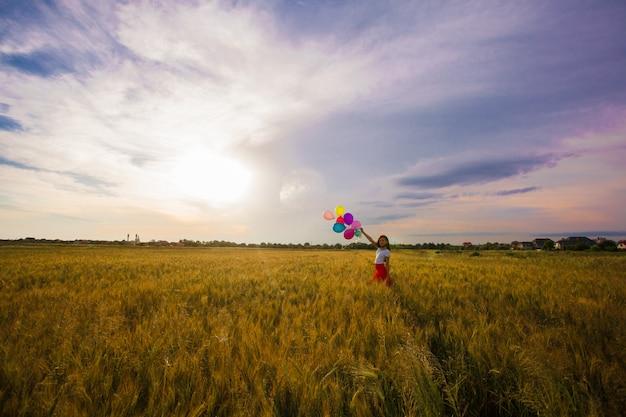 Jovem com uma saia vermelha correndo com balões coloridos no campo de trigo. inspiração da natureza, luz de fundo