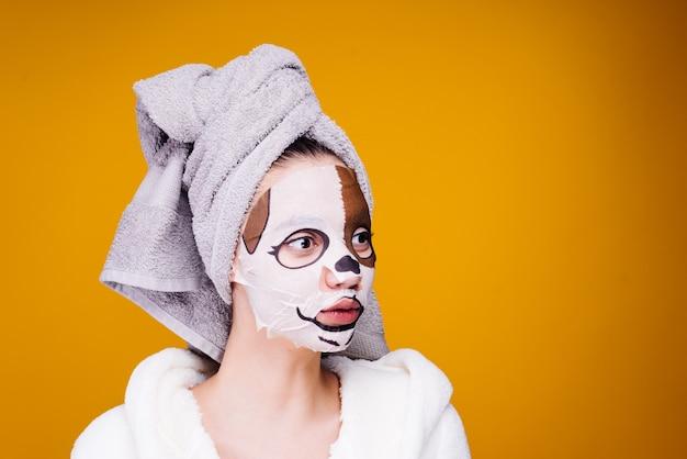 Jovem com uma toalha na cabeça, máscara facial com cara de cachorro