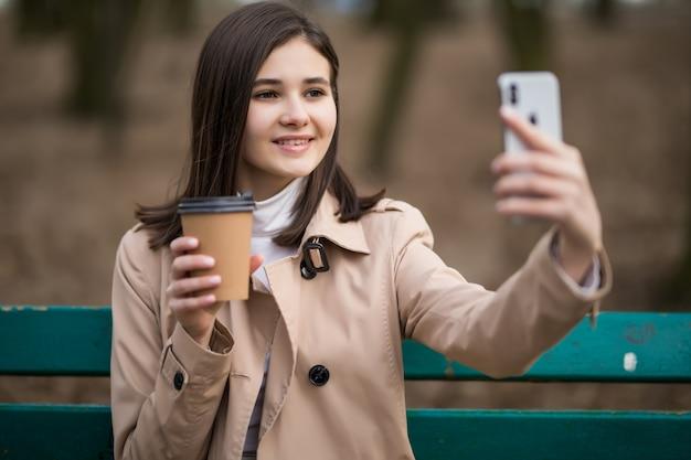 Jovem com uma xícara de café faz selfie no parque outono