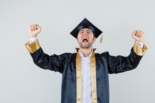 Jovem com uniforme de pós-graduação, mostrando o gesto do vencedor e parecendo com sorte, vista frontal.