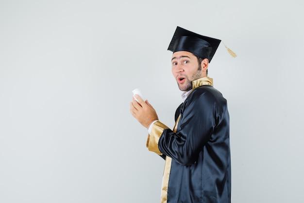 Jovem com uniforme de pós-graduação segurando um frasco de comprimidos e parecendo surpreso